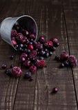 Gefrorene Beeren mischen in einer schwarzen Schüssel auf hölzernem Hintergrund Lizenzfreies Stockfoto
