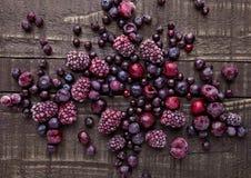 Gefrorene Beeren mischen im kleinen Stahleimer auf Holztisch Stockfotos