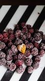 Gefrorene Brombeere mit einem Herz-förmigen kleinen Kuchen auf einem gestreiften gestreiften Hintergrund stockfoto