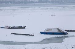 Gefrorene Donau auf Eis, kleine Fischerboote Stockfotos