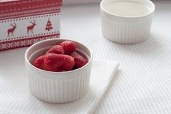 Gefrorene Erdbeeren in einer weißen Platte auf einer weißen Tischdecke auf dem Hintergrund des Weihnachtsgeschenks Stockbilder