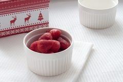 Gefrorene Erdbeeren in einer weißen Platte auf einer weißen Tischdecke auf dem Hintergrund des Weihnachtsgeschenks Lizenzfreie Stockfotos