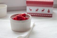 Gefrorene Erdbeeren in einer weißen Platte auf einer weißen Tischdecke nahe Weihnachtsgeschenk Stockfoto
