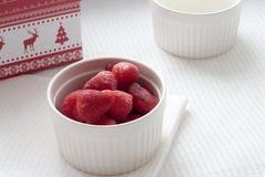 Gefrorene Erdbeeren in einer weißen Platte auf einer weißen Tischdecke nahe Weihnachtsgeschenk Lizenzfreie Stockfotografie