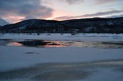 Gefrorene Flusslandschaft mit sonnigem rosa Glühen und Reflexion Stockbild