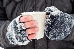 Gefrorene Hände, die einen Becher halten Stockfotos