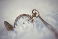 Gefrorene Koniferenniederlassungen mit Taschenuhr im weißen Winter, im Winter- und guten Rutsch ins Neue Jahr-Hintergrund Stockbilder