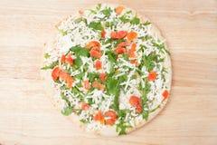 Gefrorene Pizza auf hölzernem Brett Stockfoto