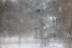 Gefrorene Tropfen auf Mattglas. Strukturierter Hintergrund des Winters. Stockfotos