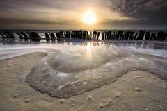 Gefrorene Wellen durch Wellenbrecher bei Sonnenuntergang stockbild