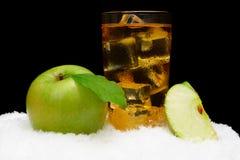 Gefrorener Apfelsaft, Eiswürfel und Apfel mit Blättern auf Schwarzem auf Schnee Stockbild