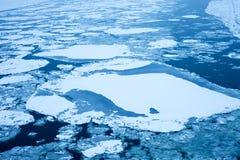 Gefrorener Fluss mit Klumpen des Eises Stockfoto