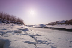 Gefrorener Fluss am Sonnenuntergang Stockfotos