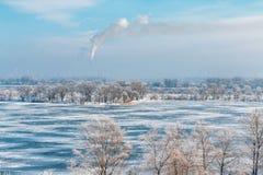 Gefrorener Fluss und der Rauch vom Kamin in der Stadt stockbild