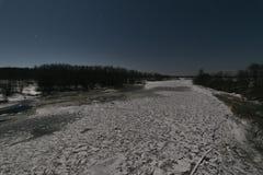 Gefrorener Fluss unter Mondschein stockfotografie