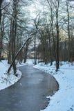 Gefrorener gebogener Abzugsgraben im Park im Schnee Lizenzfreie Stockfotos
