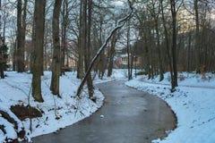 Gefrorener gebogener Abzugsgraben im Park im Schnee Stockfoto