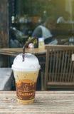Gefrorener Kaffee in der Mitnehmerschale auf hölzerner Tabelle mit unscharfem Kaffeecaféhintergrund, Lichteffekt fügte, selektive Stockfotografie