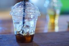 Gefrorener Kaffee in einer transparenten Plastikschale mit einem schwarzen Stroh Lizenzfreies Stockbild