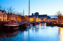 Gefrorener Kanal mit Schiffen in Groningen in der Dämmerung Lizenzfreies Stockbild