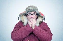 Gefrorener Mann in der Winterkleidung und -gläsern, die Hände, Kälte, Schnee, Blizzard wärmen Stockfoto