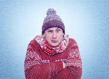 Gefrorener Mann in Erwärmungshänden der Strickjacke, des Schals und des Hutes, Kälte, Schnee, Blizzard Stockfotos