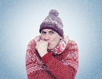 Gefrorener Mann in Erwärmungshänden der Strickjacke, des Schals und des Hutes, Kälte, Schnee, Blizzard Stockbild