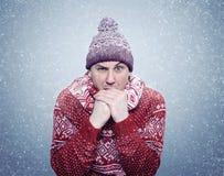 Gefrorener Mann in Erwärmungshänden der Strickjacke, des Schals und des Hutes, Kälte, Schnee, Blizzard Stockfoto