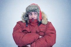 Gefrorener Mann im Winter kleidet Erwärmungshände, Kälte, Schnee, Blizzard Stockbild