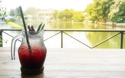 Gefrorener roselle Saft im Glas mit roselle Frucht auf Holztisch und Seeblick für gesundes lizenzfreie stockfotografie