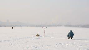 Gefrorener See in der Stadt mit Fischern in den Hintergrundhäusern, Eisfischen stockfotos