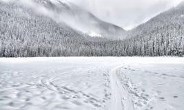 Gefrorener See mit Schlitten-Spur in den Bergen Lizenzfreies Stockbild