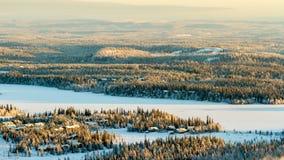 Gefrorener See und gezierter Wald im Winter Finnland, Ruka stockfotos