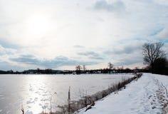 Gefrorener Teich mit Schneestellen Stockfotografie