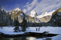 Gefrorener Teich vor Gebirgsoberseite Stockfotos