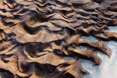 Gefrorener und eisiger Flussgrund im Sonnenlicht Stockfotografie