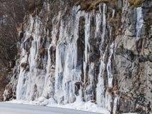 Gefrorener Wasserfall, der von einer steilen Felsenklippe taucht Lizenzfreies Stockfoto