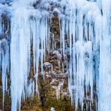 Gefrorener Wasserfall von blauen Eiszapfen Lizenzfreies Stockfoto