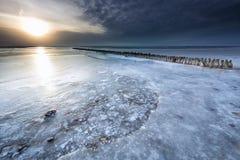 Gefrorener Wellenbrecher auf großem See im Winter stockbilder