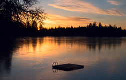 Gefrorener Wintersee bei Sonnenuntergang Stockfotos