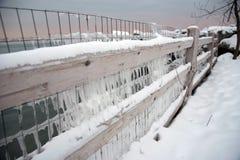 Gefrorener Zaun bedeckt in den Eiszapfen entlang Michigansee im Winter stockfotos