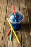 Gefrorenes blaues Slushie in der Plastikschale mit Strohen Stockfotos