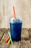 Gefrorenes blaues Slushie in der Plastikschale mit Strohen Lizenzfreie Stockbilder