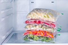Gefrorenes Gemüse in den Taschen im Kühlschrank stockbilder