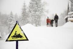 Gefrorenes Schneemobil fahrung Zeichen und Fogy, schneebedeckter Hintergrund mit gehender Familie lizenzfreie stockbilder