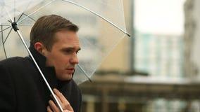 Gefrustreerd door het weer, die zich onder de paraplu tijdens de regen bevinden Ongelukkige mens in een kostuum stock videobeelden
