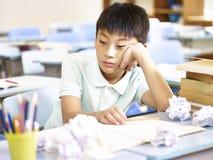 Gefrustreerde Aziatische schooljongen stock fotografie