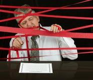 Gefrustreerde bedrijfsdiemens in bureaucratische formaliteiten wordt gevangen die vooruitgang tegenhouden stock foto
