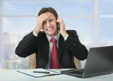 Gefrustreerde bedrijfsmens die op telefoon spreekt stock foto's