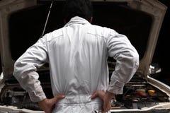 Gefrustreerde beklemtoonde jonge mechanische mens in wit eenvormig die gevoel of uitgeput met auto in open kap bij reparatiegara  stock foto